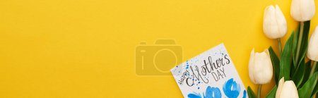 Photo for Top view of spring tulips and happy mothers day greeting card on colorful yellow background, panoramic shot - Royalty Free Image