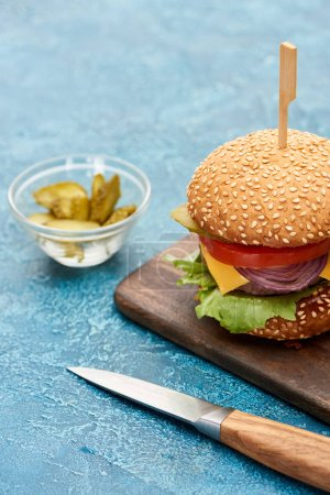 selective focus of delicious cheeseburger on wooden board near pickles and knife on blue textured surface