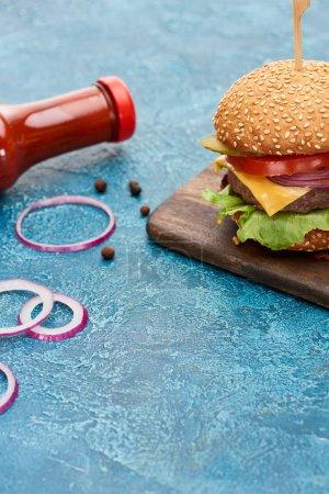 Photo pour Délicieux cheeseburger sur planche de bois près de l'oignon et ketchup sur surface texturée bleue - image libre de droit
