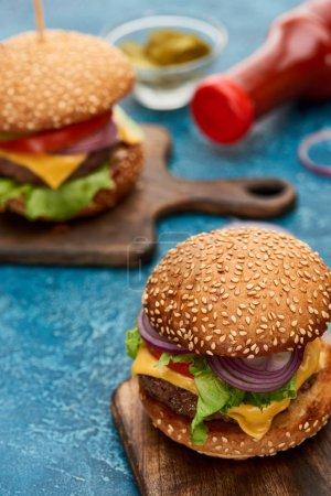 Photo pour Foyer sélectif de délicieux cheeseburger sur planche de bois sur surface texturée bleue - image libre de droit