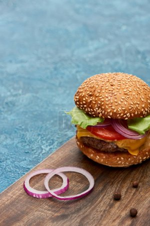 Photo for Delicious cheeseburger on wooden board with onion on blue textured surface - Royalty Free Image