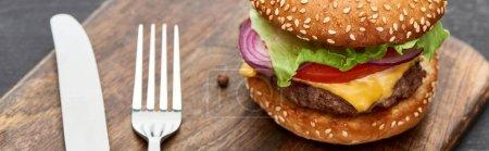 Photo pour Vue rapprochée de délicieux cheeseburger frais sur planche en bois avec couverts, vue panoramique - image libre de droit
