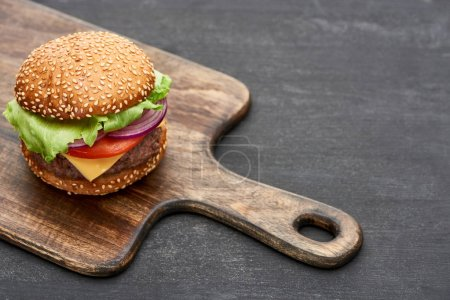 Photo for Delicious fresh cheeseburger on wooden board on grey surface - Royalty Free Image
