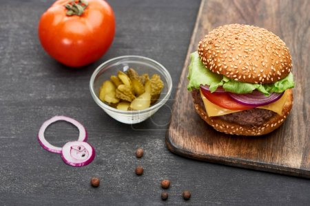 Photo for Delicious fresh cheeseburger on wooden board near tomato, pickles and onion rings - Royalty Free Image