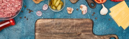 Photo pour Top view of fresh burger ingredients near empty cutting board on blue textured surface, panoramic shot - image libre de droit