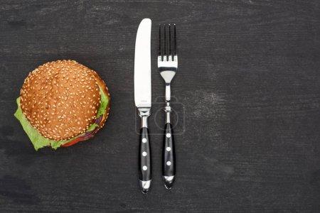 Photo pour Top vue de délicieux hamburgers frais sur table noire en bois avec couteau et fourchette - image libre de droit