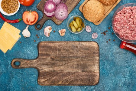 Photo pour Top view of fresh burger ingredients near empty cutting board on blue textured surface - image libre de droit