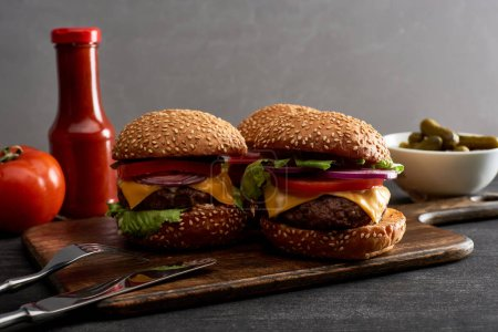 Photo for Delicious fresh meat cheeseburgers on wooden board near cutlery, ingredients and ketchup - Royalty Free Image