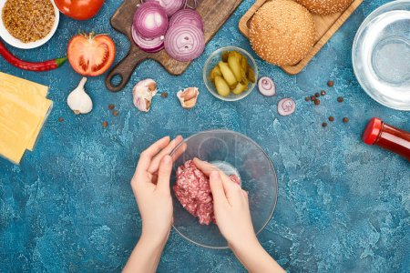 Photo pour Top view of woman holding bawl with raw minced meat near fresh burger ingredients on blue textured surface - image libre de droit
