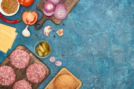 Photo pour Top view of fresh burger ingredients on blue textured surface with copy space - image libre de droit