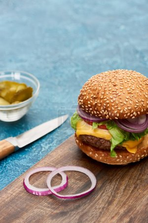 Photo pour Foyer sélectif de délicieux cheeseburger sur planche de bois près des cornichons et couteau sur surface texturée bleue - image libre de droit