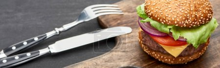 Photo for Delicious fresh cheeseburger on wooden board near cutlery, panoramic shot - Royalty Free Image