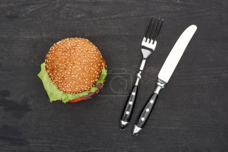 Photo for Tasty fresh burger on wooden black table with cutlery - Royalty Free Image
