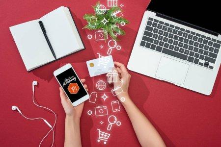 Photo pour Vue en coupe d'une femme tenant une carte de crédit et un téléphone intelligent avec illustration de magasinage en ligne près d'un ordinateur portable, d'écouteurs, d'un stylo, d'un bloc-notes et d'une plante sur fond rouge - image libre de droit