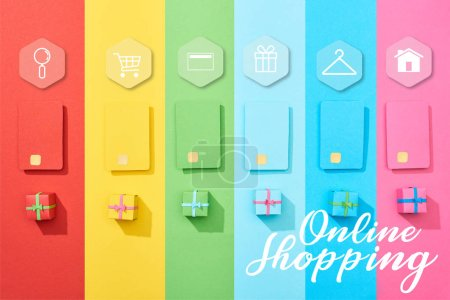 Photo pour Top view of multicolored empty credit cards and gift boxes on rainbow background with online shopping illustration - image libre de droit