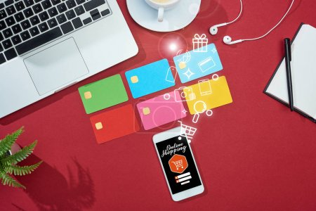 top view of multicolored empty credit cards on red background with online shopping illustration on smartphone near laptop, earphones and coffee