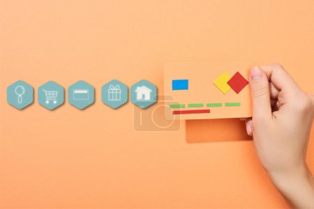 cropped view of woman holding credit card template on peach background with icons illustration
