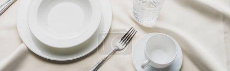 Photo pour Vue grand angle de la vaisselle avec verre et tasse à café sur nappe blanche, vue panoramique - image libre de droit