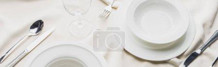 Photo pour Vue panoramique de la vaisselle de service avec verre à vin sur la nappe blanche - image libre de droit