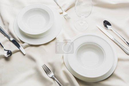 Foto de Vista de gran angular de la vajilla con cubertería y vaso de vino sobre manteles ondulados. - Imagen libre de derechos