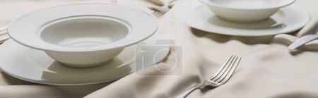 Photo pour Servir de la vaisselle sur une nappe blanche ondulée, panoramique - image libre de droit