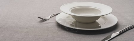 Two plates and cutlery on grey surface, panoramic shot
