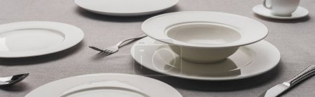 Selective focus of serving tableware with coffee cup on grey tablecloth, panoramic shot
