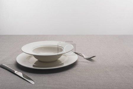Photo pour Plaques avec fourchette et couteau sur nappe sur fond gris - image libre de droit