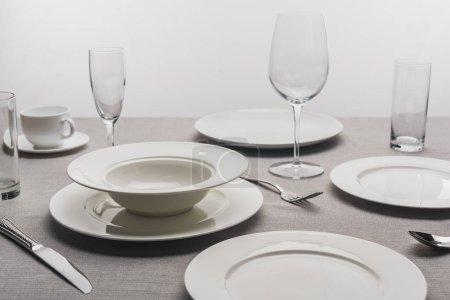 Photo pour Vaisselle et verres transparents sur nappe sur fond gris - image libre de droit