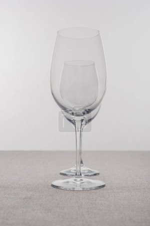 Photo for Selective focus of transparent wine glasses on tablecloth isolated on grey - Royalty Free Image
