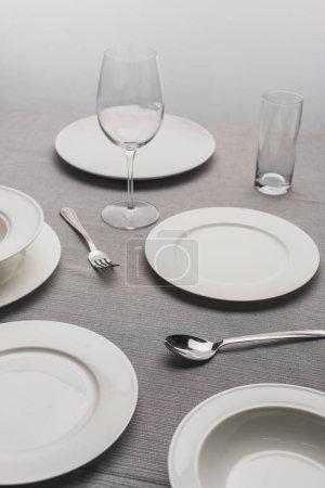 Photo pour Servir la vaisselle avec des verres vides sur la surface grise - image libre de droit
