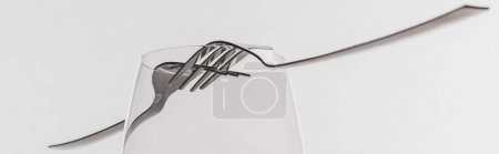 Panoramic shot of forks on clear wine glass isolated on grey