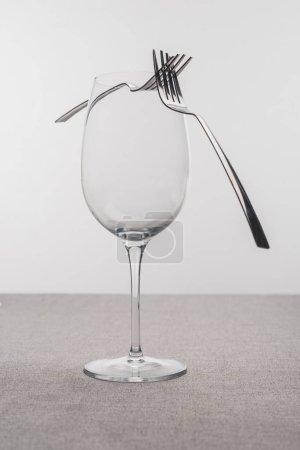 Photo pour Deux fourchettes sur verre à vin transparent sur nappe isolée sur gris - image libre de droit