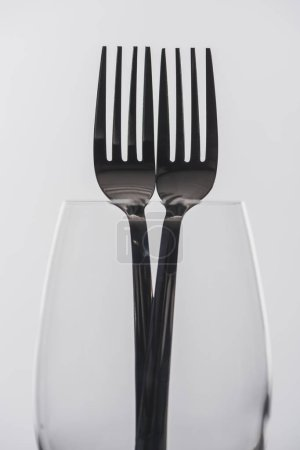 Selective focus of forks in transparent wine glass isolated on grey