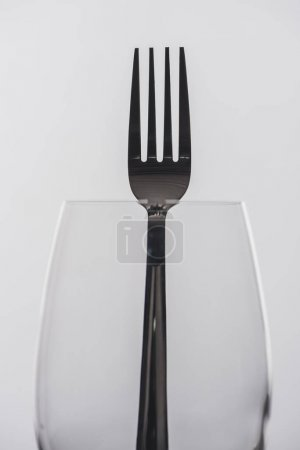 Selective focus of fork in wine glass isolated on grey