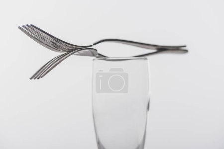 Selective focus of forks on clear champagne glass isolated on grey