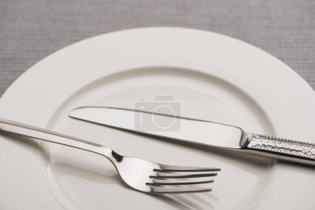 Photo for Close up view of cutlery on empty plate on grey surface - Royalty Free Image