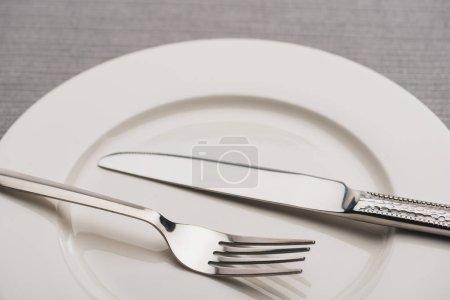 Nahaufnahme von Besteck auf leerem Teller auf grauer Oberfläche