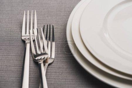 leere Teller mit Gabeln auf grauem Leinentischtuch