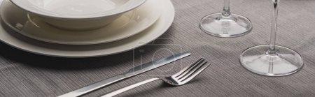 Photo pour Servir des assiettes avec couverts et verres à vin sur toile grise, plan panoramique - image libre de droit