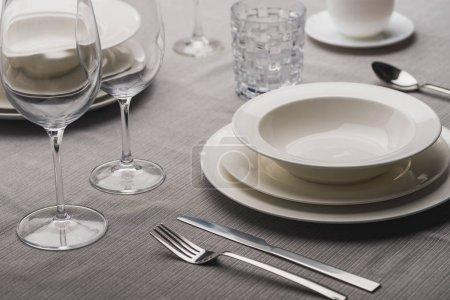 Photo pour Servir la vaisselle avec la coutellerie et les verres sur la nappe en lin gris - image libre de droit
