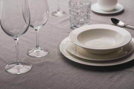 Photo pour Servir de la vaisselle avec des verres à vin sur une nappe grise - image libre de droit