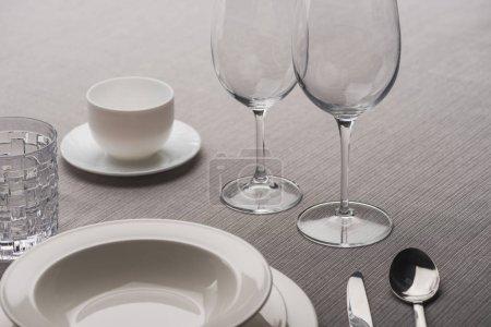 Photo pour Verres à vin clair à côté de vaisselle et tasse de café sur toile grise - image libre de droit
