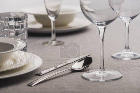 Photo pour Choix de la vaisselle à servir sur une nappe grise - image libre de droit