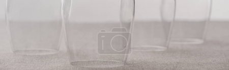 Photo for Panoramic shot of clear wine glasses on tablecloth isolated on grey - Royalty Free Image