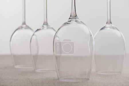 Photo pour Concentration sélective des verres à vin transparents sur la nappe isolée sur gris - image libre de droit