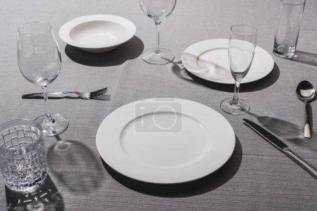 Photo pour Vide vaisselle de service avec verres sur tissu gris - image libre de droit