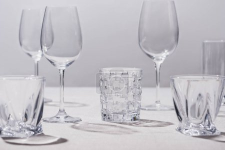 Empty glasses on white tablecloth isolated on grey