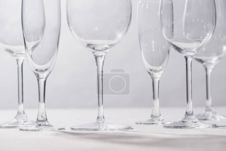 Photo for Shiny clear glasses on white surface isolated on grey - Royalty Free Image