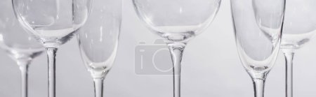 Panoramic shot of transparent glasses isolated on grey